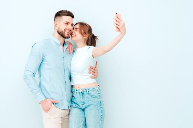 Mulher bonita sorridente e seu namorado bonito. família feliz e alegre tendo momentos de ternura perto de uma parede azul clara em estúdio
