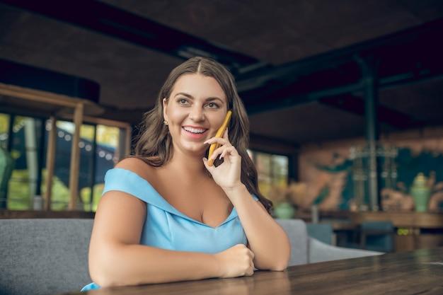 Mulher bonita sorridente em um vestido azul com smartphone perto de orelha, sentada à mesa em um café de verão e de ótimo humor