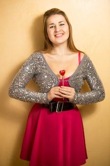 Mulher bonita sorridente em um vestido rosa segurando um coração decorativo em um palito