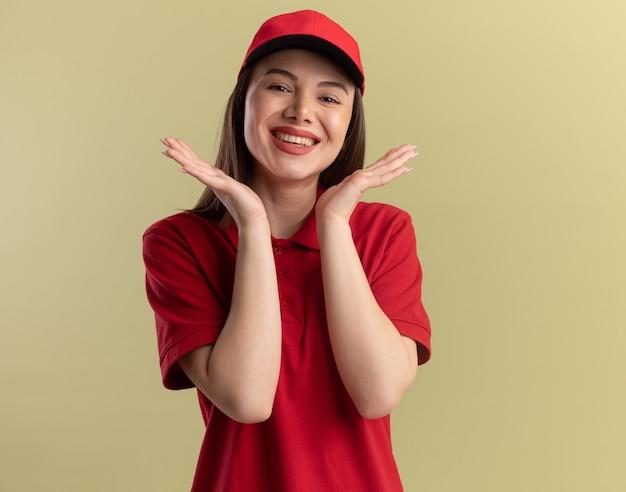 Mulher bonita sorridente entregadora de uniforme de mãos dadas perto do rosto, isolada na parede verde oliva com espaço de cópia