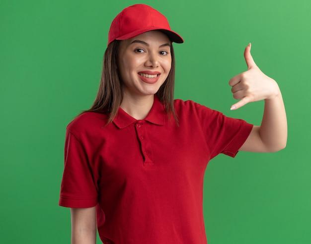 Mulher bonita sorridente, entregadora de uniforme, gesticulando para pendurar a placa isolada na parede verde com espaço de cópia