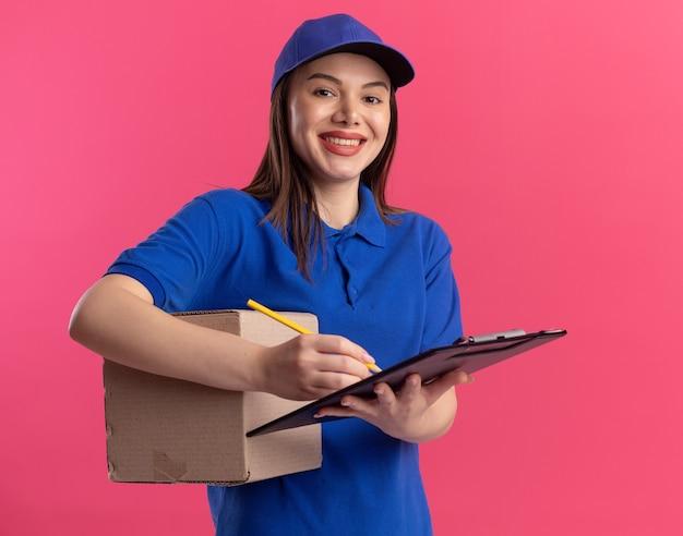 Mulher bonita sorridente, entregadora de uniforme, segurando uma caixa de papelão escrevendo na prancheta com lápis