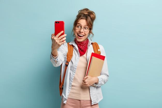 Mulher bonita sorridente faz selfie via celular, em alto astral, aproveita o tempo livre depois das aulas, usa bandana vermelha no pescoço