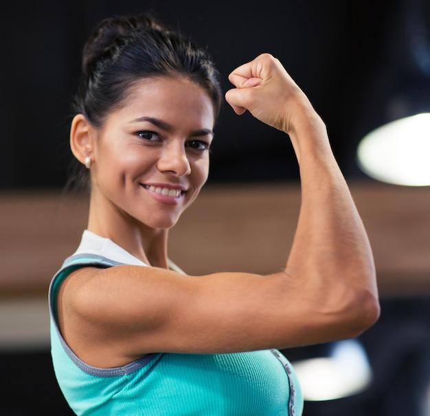 Mulher bonita sorridente mostrando seu bíceps na academia