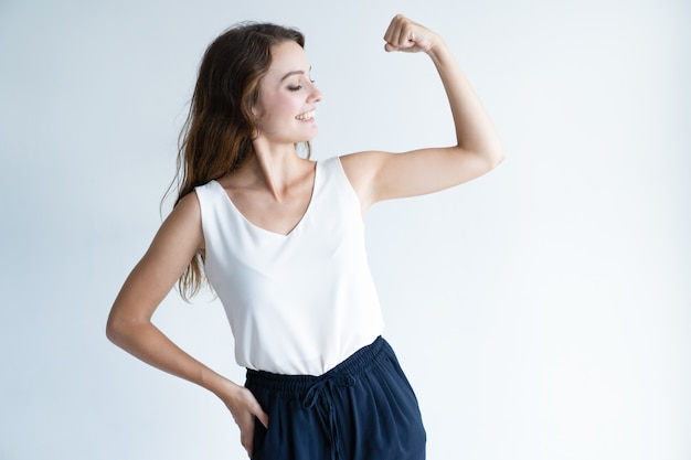 Mulher bonita sorridente, mostrando seu bíceps