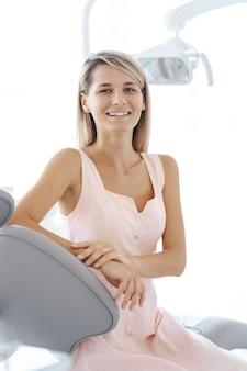 Mulher bonita sorridente na cadeira do dentista