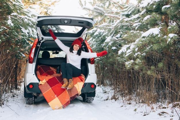 Mulher bonita sorridente na mala do carro no espaço da cópia da floresta de inverno nevado