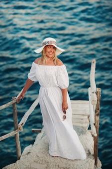 Mulher bonita sorridente na praia com um chapéu de palha na ilha de zakynthos. uma garota em um vestido branco ao pôr do sol na ilha de zakynthos, grécia