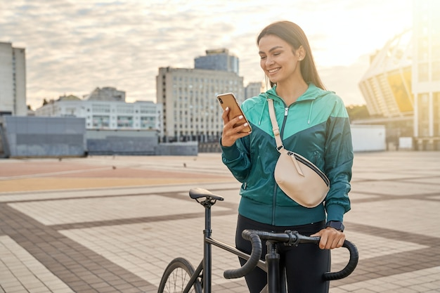 Mulher bonita sorridente olhando para a tela do smartphone ao ar livre