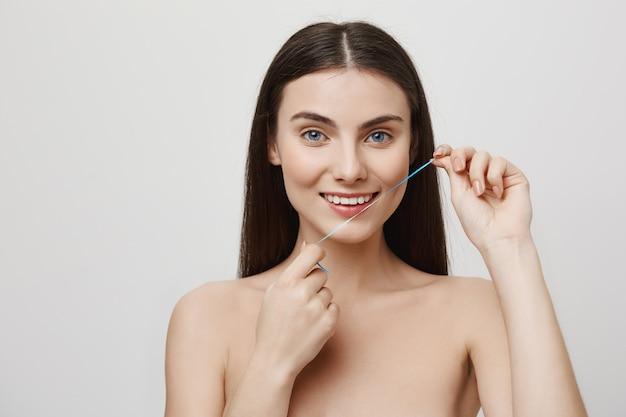 Mulher bonita sorridente passando fio dental dentes com fio dental