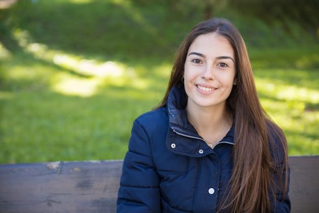 Mulher bonita sorridente posando para a câmera no parque