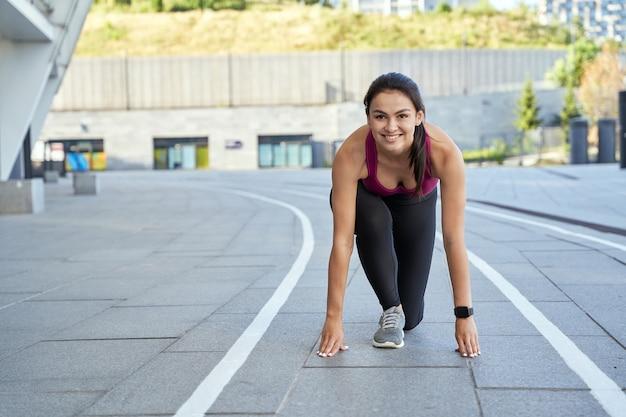 Mulher bonita sorridente se preparando para começar a correr