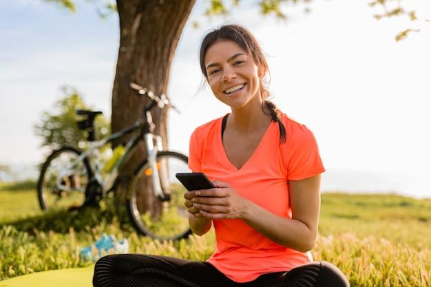 Mulher bonita sorridente segurando um telefone fazendo esportes de manhã no parque