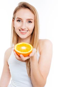 Mulher bonita sorridente segurando uma laranja e olhando para a câmera
