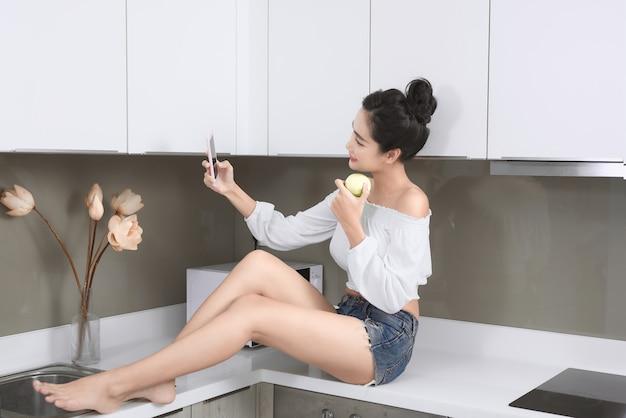 Mulher bonita sorridente tomando uma selfie com uma maçã na cozinha.