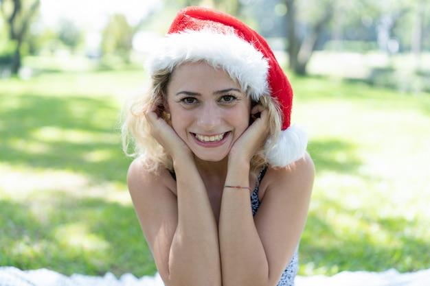 Mulher bonita sorridente usando chapéu de papai noel no parque de verão
