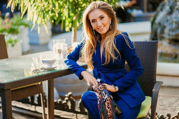 Mulher bonita sorridente, vestida com um elegante terno azul, sentada em um café em um dia ensolarado de outono