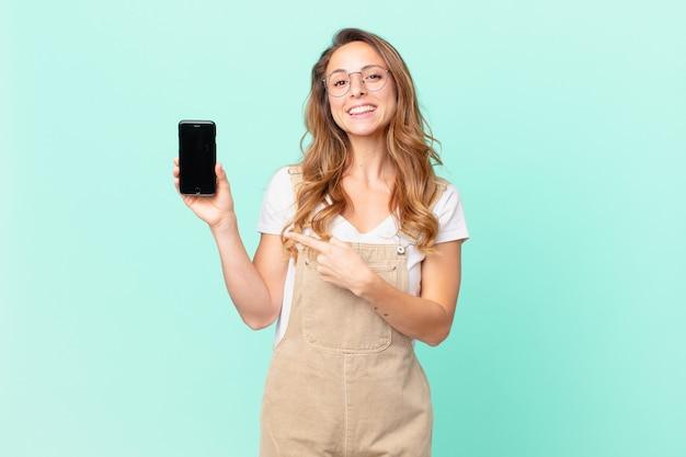 Mulher bonita sorrindo alegremente, feliz, apontando para o lado e segurando um smartphone