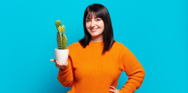 Mulher bonita sorrindo alegremente segurando uma planta
