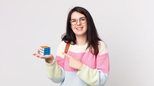 Mulher bonita sorrindo alegremente, sentindo-se feliz e apontando para o lado resolvendo um jogo de inteligência