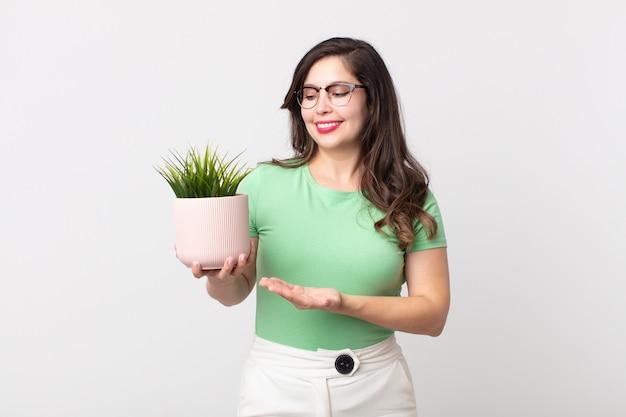Mulher bonita sorrindo alegremente, sentindo-se feliz e mostrando um conceito e segurando uma planta decorativa