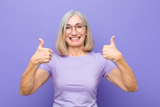 Mulher bonita sorrindo amplamente olhando feliz, positivo, confiante e bem sucedido, com os dois polegares para cima