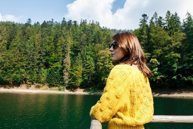 Mulher bonita sorrindo, apreciando a vista das montanhas, lago e floresta