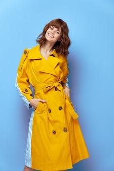 Mulher bonita sorrindo com as mãos nos bolsos de um casaco amarelo lábios vermelhos estilo de vida