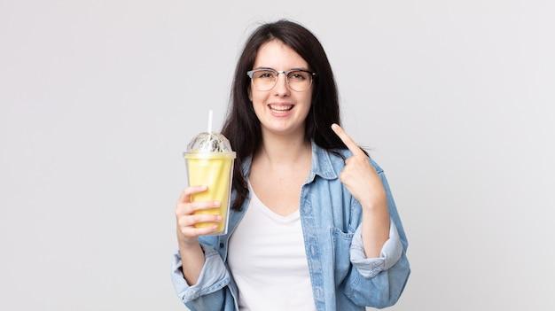 Mulher bonita sorrindo com confiança apontando para o próprio sorriso largo e segurando um milkshake de baunilha
