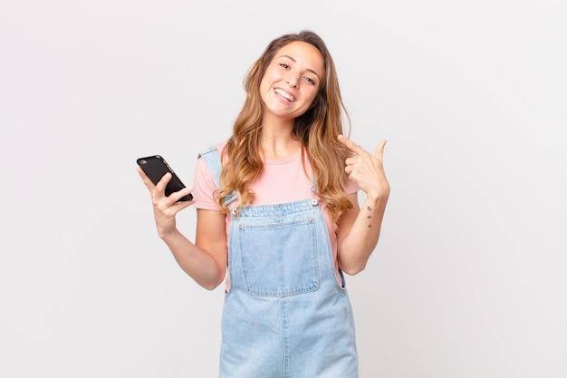 Mulher bonita sorrindo com confiança apontando para o próprio sorriso largo e segurando um smartphone