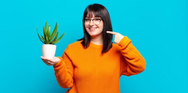 Mulher bonita sorrindo com confiança segurando uma planta