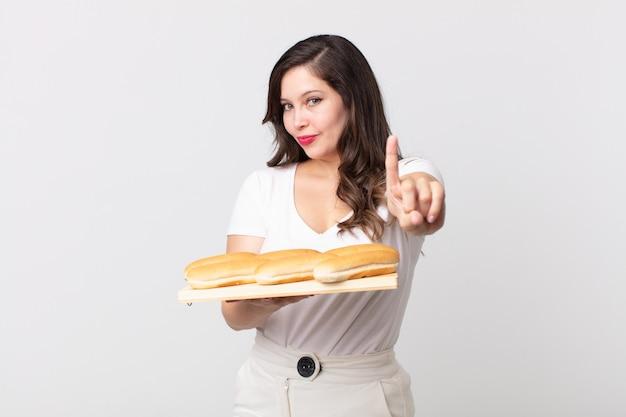 Mulher bonita sorrindo com orgulho e confiança fazendo o número um e segurando uma bandeja de pão