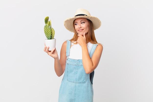 Mulher bonita sorrindo com uma expressão feliz e confiante com a mão no queixo e segurando uma planta decorativa de cacto