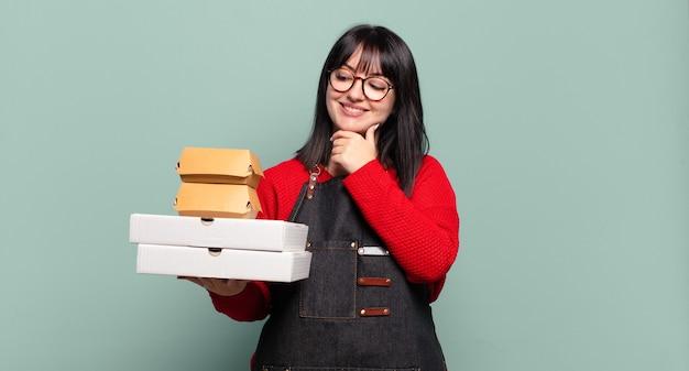 Mulher bonita sorrindo com uma expressão feliz e confiante com a mão no queixo, pensando e olhando para o lado