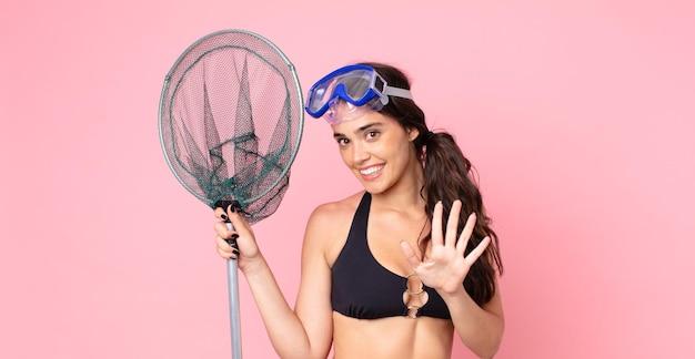 Mulher bonita sorrindo e parecendo amigável, mostrando o número cinco com óculos e uma rede de pesca