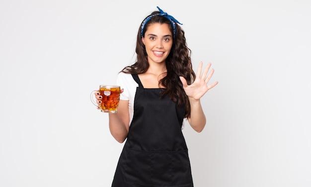 Mulher bonita sorrindo e parecendo amigável, mostrando o número cinco e segurando um copo de cerveja