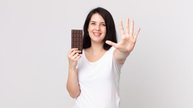 Mulher bonita sorrindo e parecendo amigável, mostrando o número cinco e segurando uma barra de chocolate
