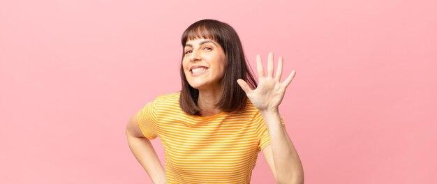 Mulher bonita sorrindo e parecendo amigável, mostrando o número cinco ou quinto com a mão para a frente, em contagem regressiva
