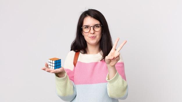 Mulher bonita sorrindo e parecendo amigável, mostrando o número dois e resolvendo um jogo de inteligência