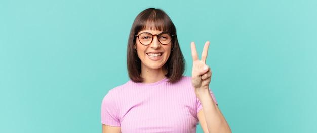 Mulher bonita sorrindo e parecendo amigável, mostrando o número dois ou o segundo com a mão para a frente, em contagem regressiva