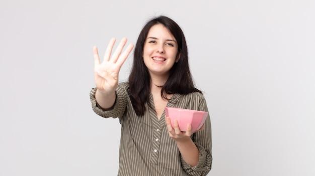 Mulher bonita sorrindo e parecendo amigável, mostrando o número quatro segurando uma tigela de panela vazia. agente assistente com fone de ouvido