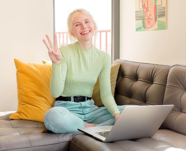 Mulher bonita sorrindo e parecendo amigável, mostrando o número três ou o terceiro com a mão para a frente, em contagem regressiva