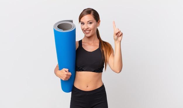 Mulher bonita sorrindo e parecendo amigável, mostrando o número um. conceito de ioga