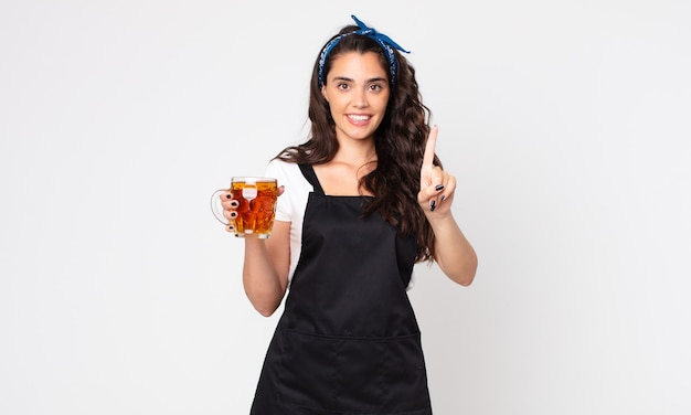 Mulher bonita sorrindo e parecendo amigável, mostrando o número um e segurando um copo de cerveja