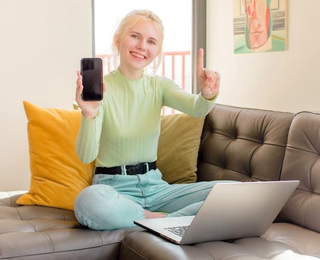 Mulher bonita sorrindo e parecendo amigável, mostrando o número um ou primeiro com a mão para a frente, em contagem regressiva