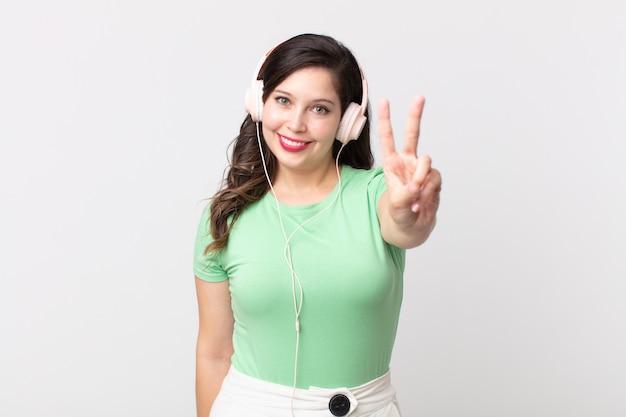 Mulher bonita sorrindo e parecendo feliz, gesticulando vitória ou paz ouvindo música com fones de ouvido