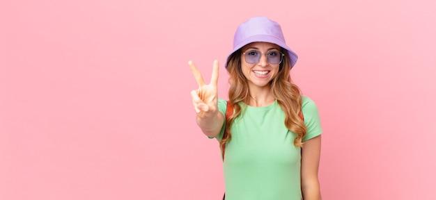 Mulher bonita sorrindo e parecendo feliz, gesticulando vitória ou paz