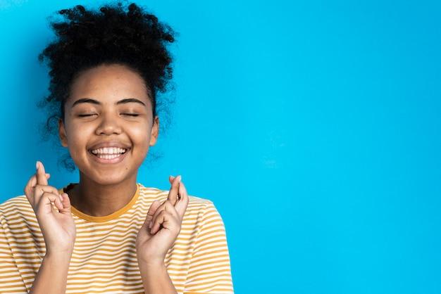Mulher bonita sorrindo e posando com os dedos cruzados