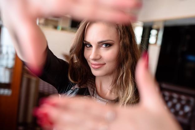 Mulher bonita sorrindo e puxando as mãos para a câmera