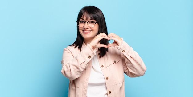 Mulher bonita sorrindo e se sentindo feliz, fofa, romântica e apaixonada, fazendo formato de coração com as duas mãos